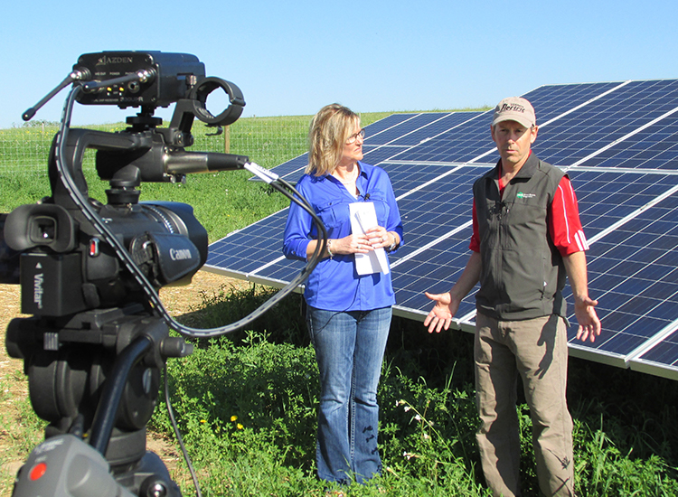 community channel 14 Interviewing two people talking in front of solar panels