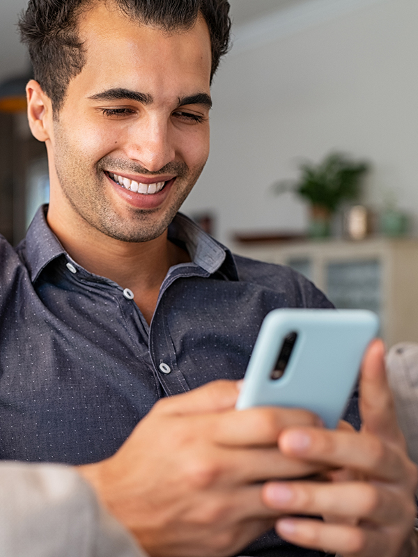 Man smiling while using his smartphone