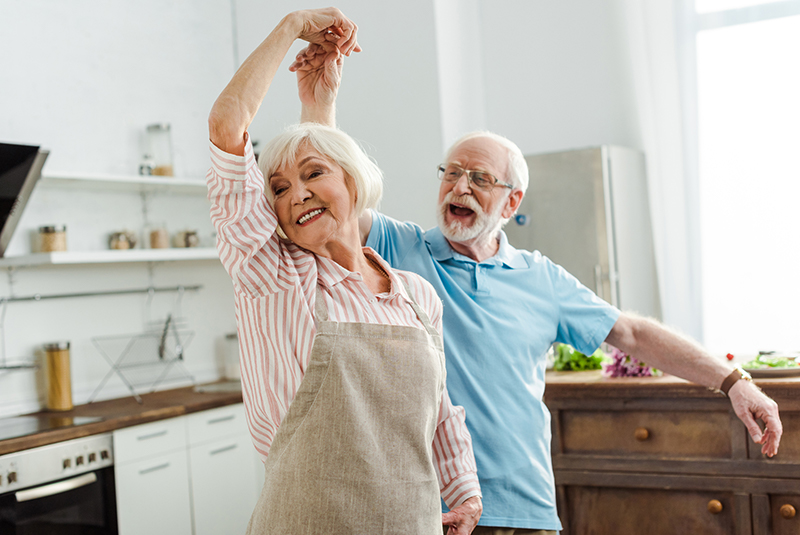 An elderly couple dancing in their kitchen while they cook dinner