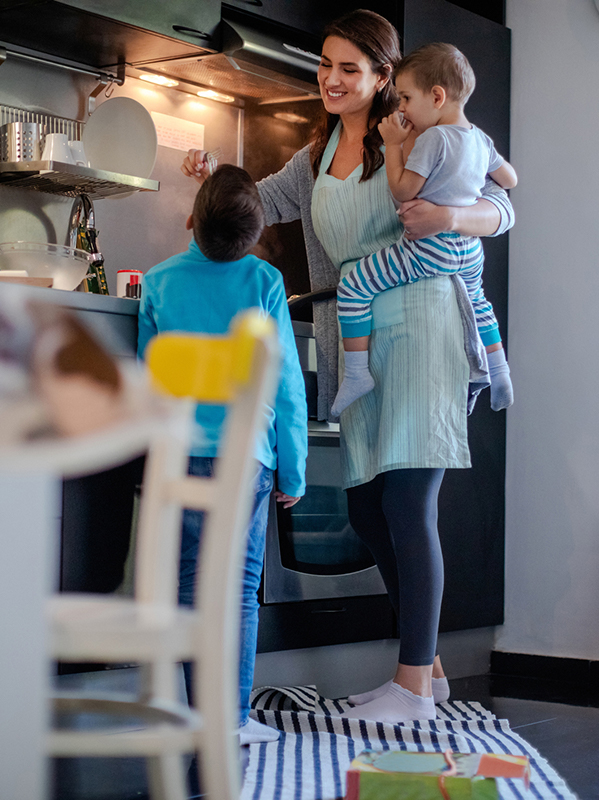 Mother in the kitchen holding a young child on her hip while she lets her other child taste the meal she's cooking