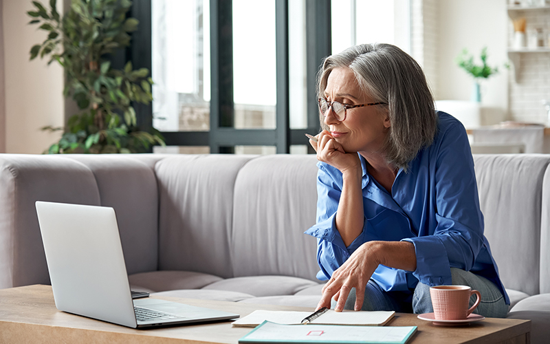 Elderly woman sitting on her sofa looking at paperwork and her laptop at her account