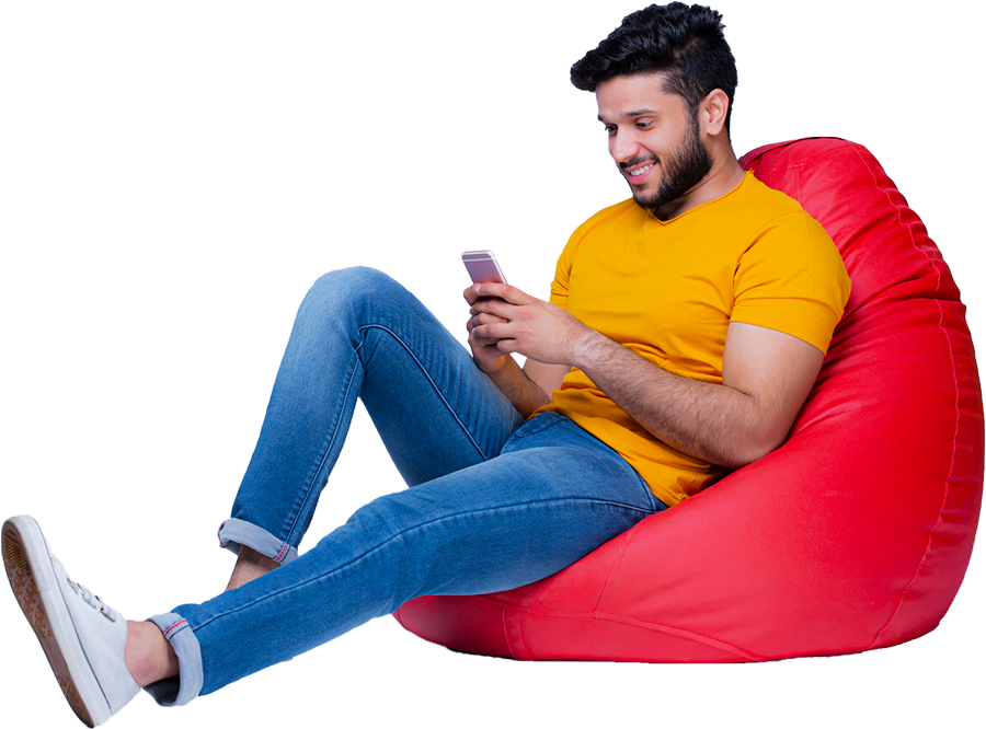 Young man sitting on a beanbag chair looking at his smartphone