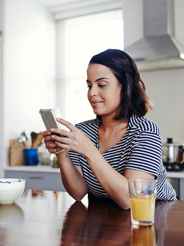 Woman in her kitchen with a glass of orange juice using her smartphone