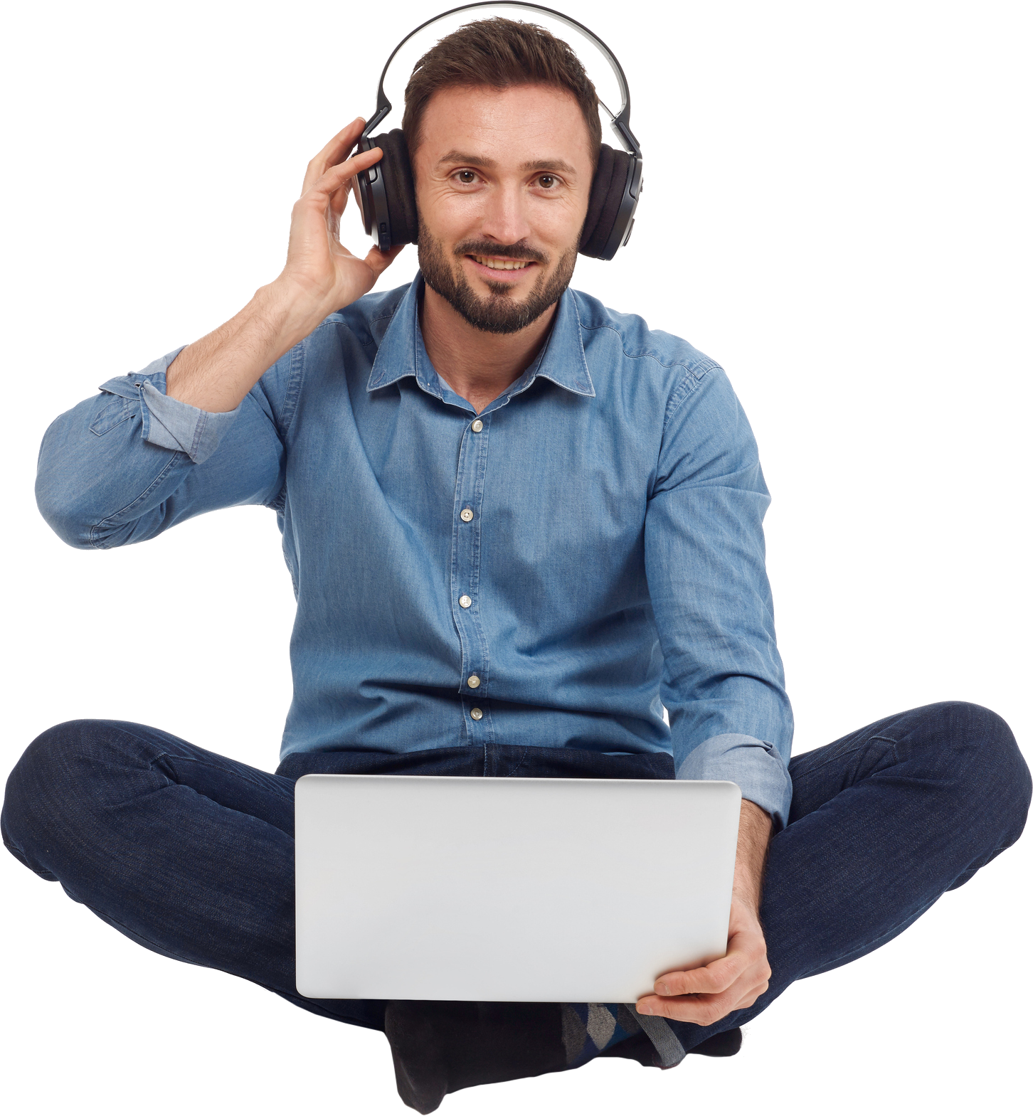 Man sitting crossed legged with headphones one and holding his laptop
