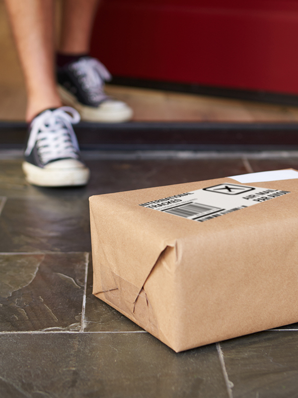package sitting on the front doorstep with a person coming out of the home to pick it up